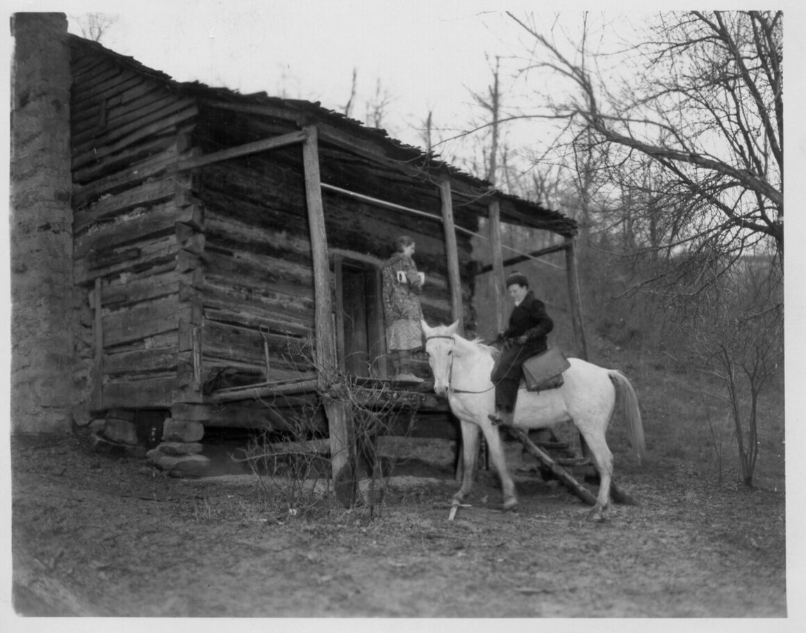 A packhorse librarian leaving a cabin after delivering books, Kentucky, c. 1930s.