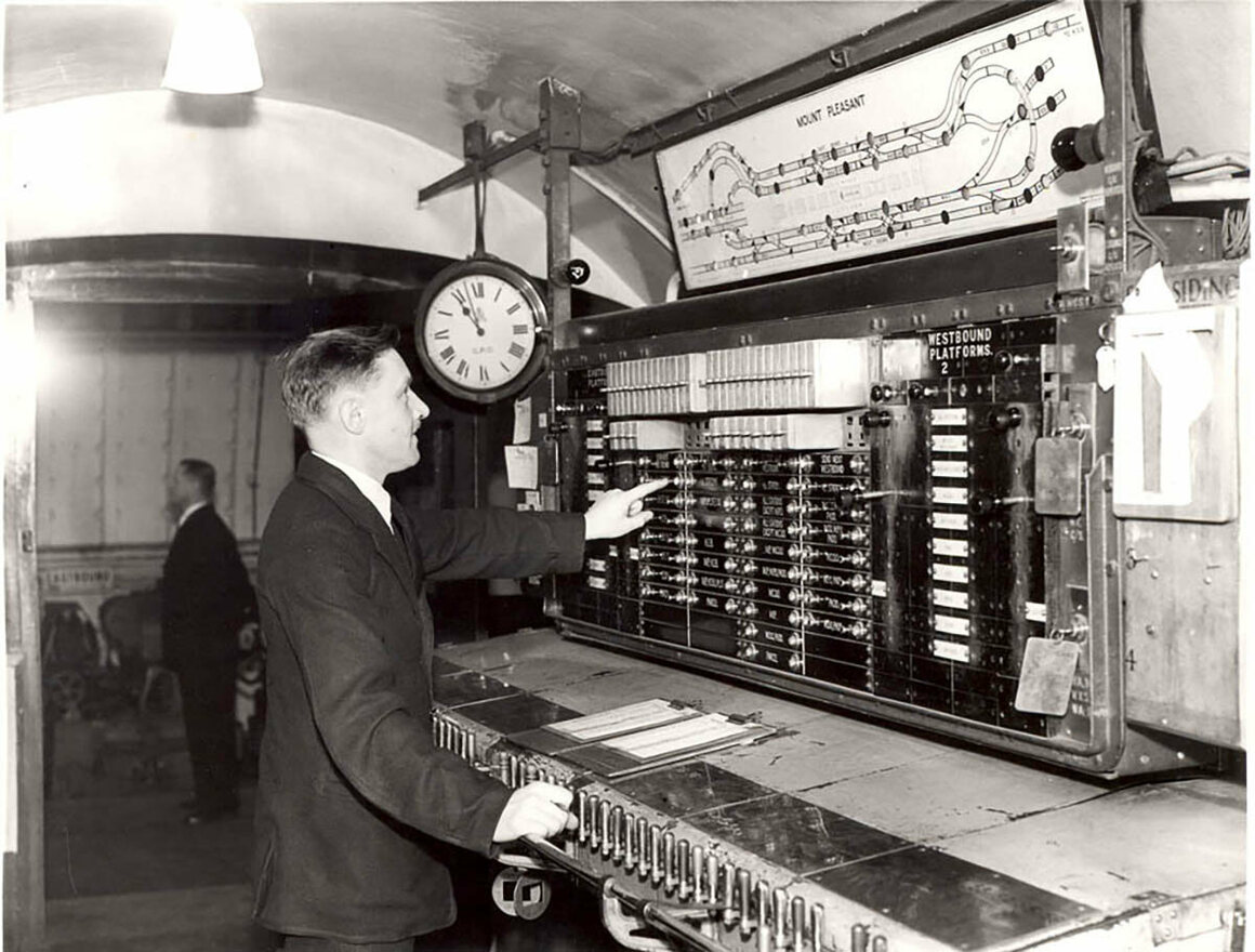 A postman operates the underground mail route control panel, c. 1935.