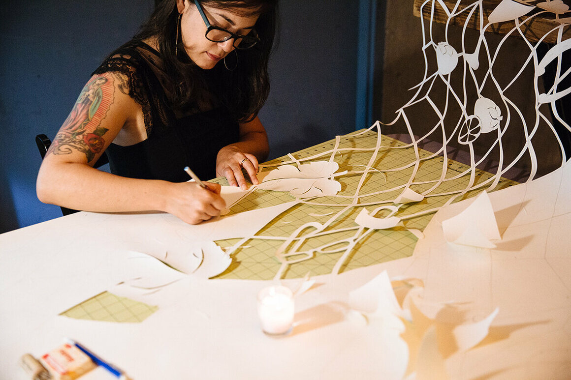 Local artist Lauren Iida creates verdant worlds that blossom from intricately cut reams of paper.