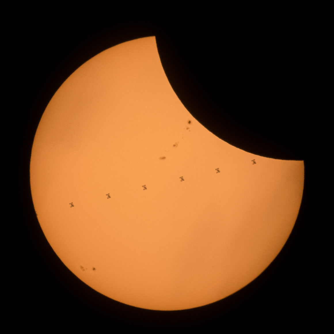 The International Space Station crosses the solar disk during the eclipse.