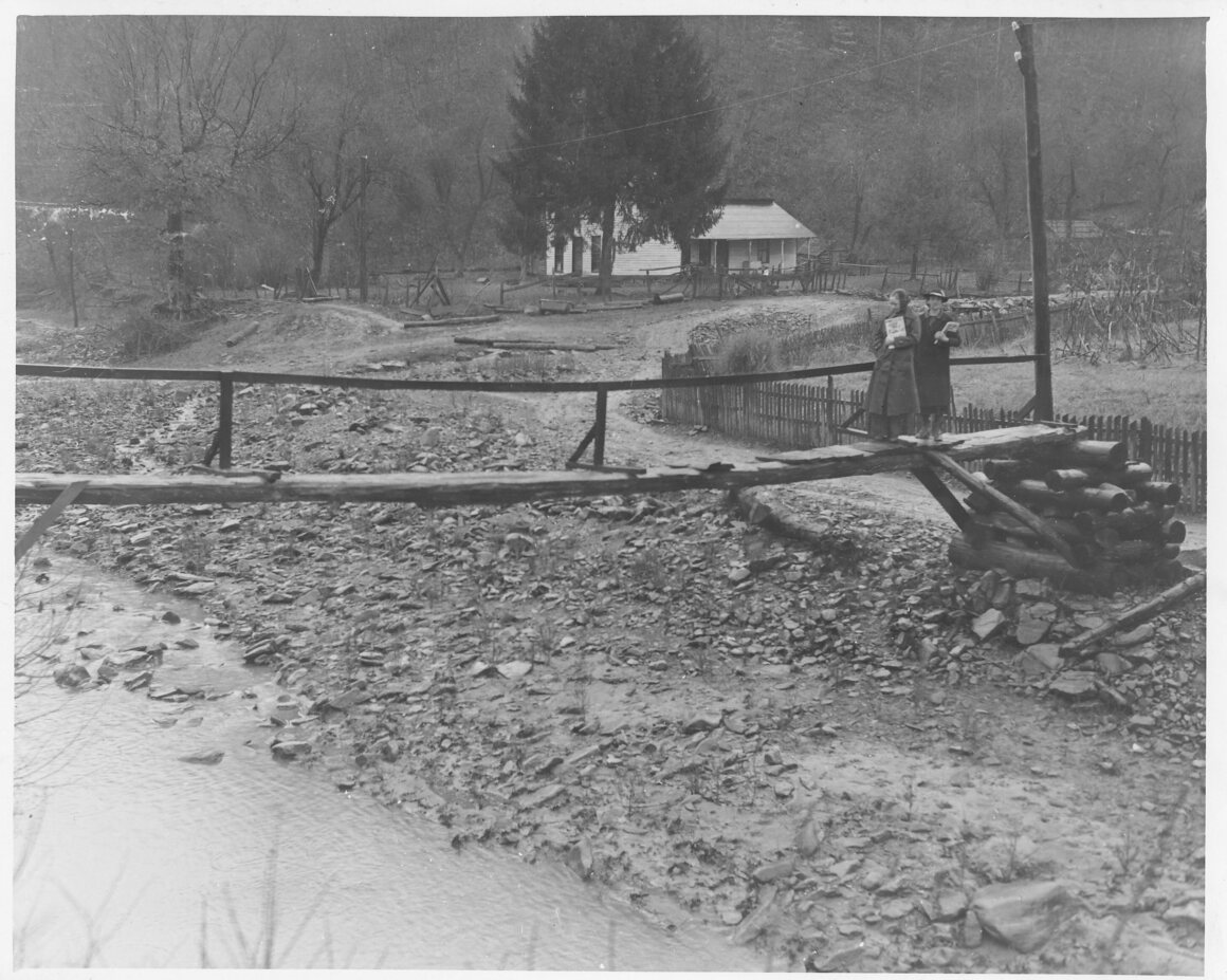 Pack horse librarians cross a log bridge to reach home used as a distribution center for a mountain community, year unknown.