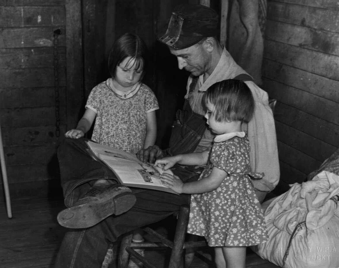 A man reading to two small children, c. 1940.