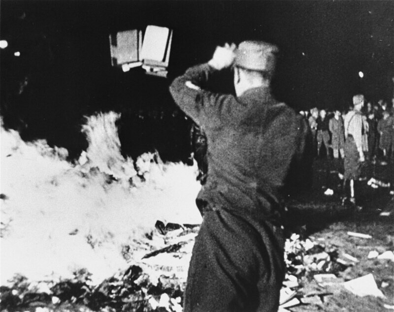 "A member of the paramilitary Nazi Sturmabteilung throws confiscated books into a bonfire during the public burning of ""un-German"" books in Berlin in 1933."