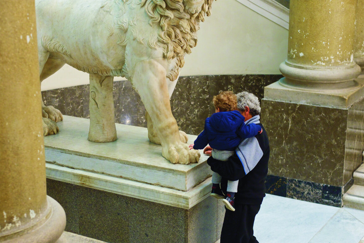 A child pets a lion's paw at the Museo Archeologico in Naples.