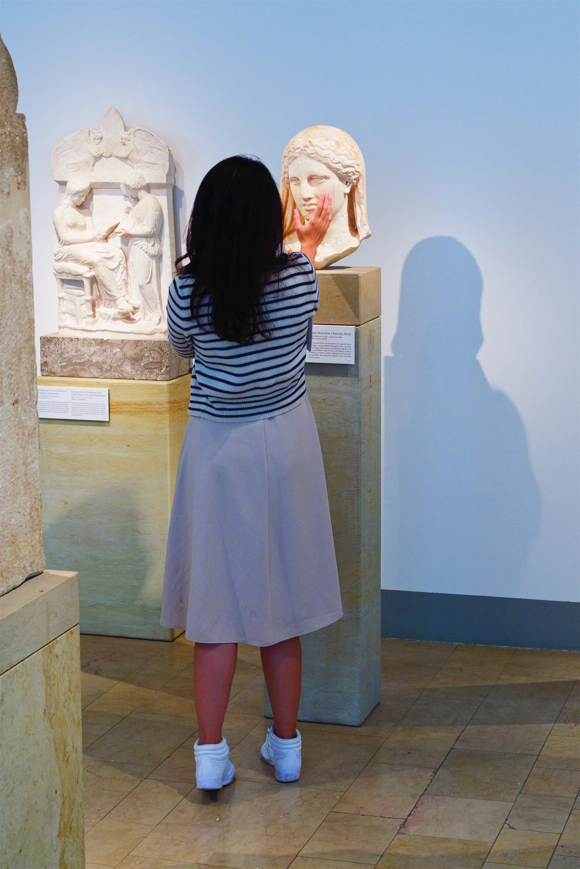 A visitor cups the face of a bust at the Altes Museum in Berlin.