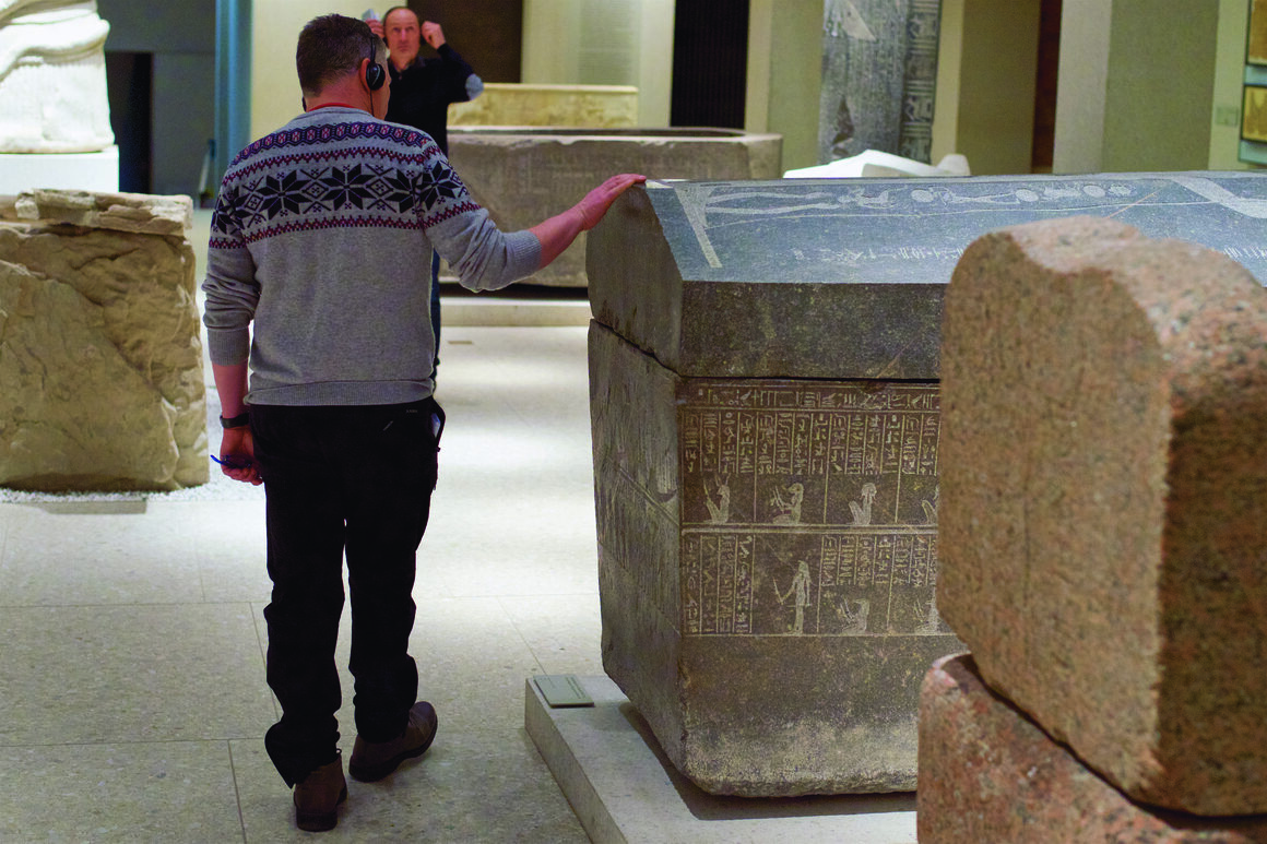 A man runs his hand along a carved sarcophagus at the Neues Museum in Berlin.