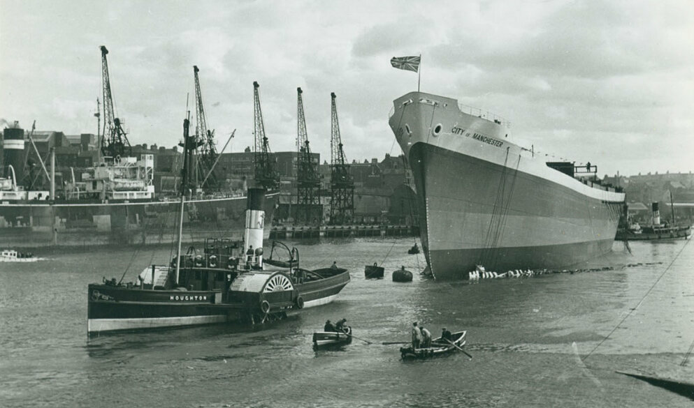 The cargo ship <em>City of Manchester</em> being towed after launch, on the River Wear in the North East England, 1949.