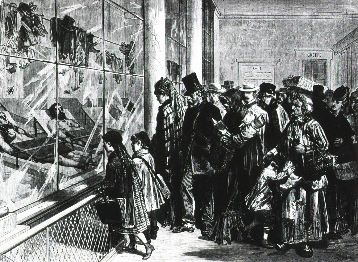 A group of people, including children, looking through glass to identify cadavers (a double suicide from England) on view.