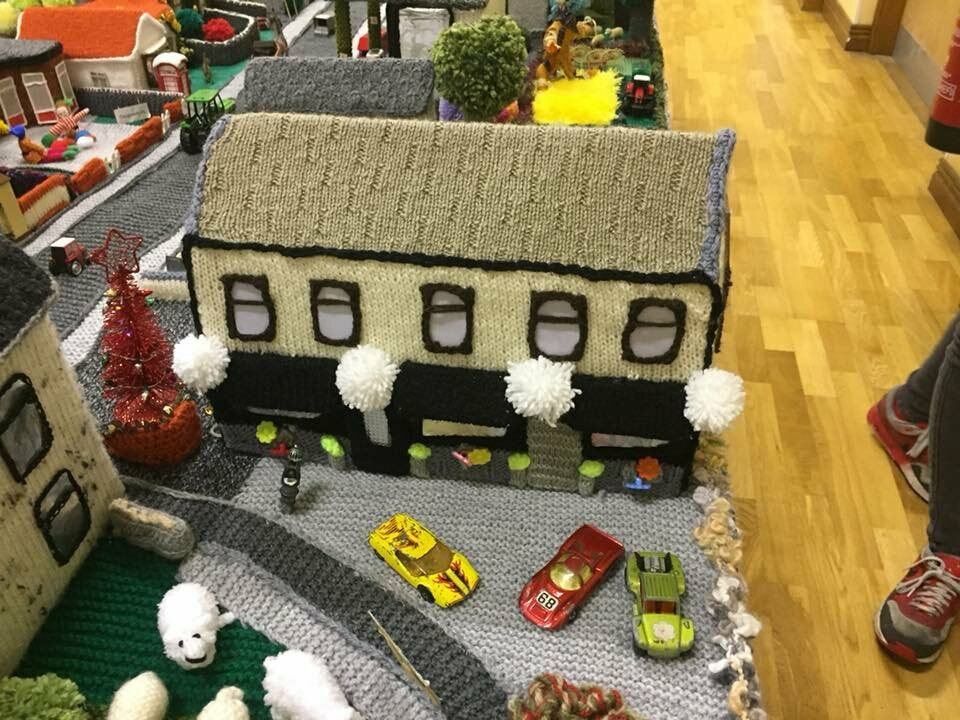 Model cars are interspersed throughout the village.