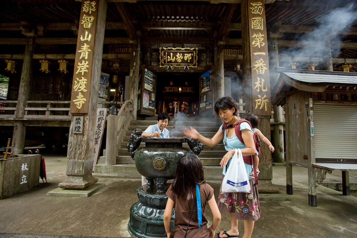 Mother teaching her young children the ritual practice of offering incense in front of the main shrine at Kumano Nachi Taisha.