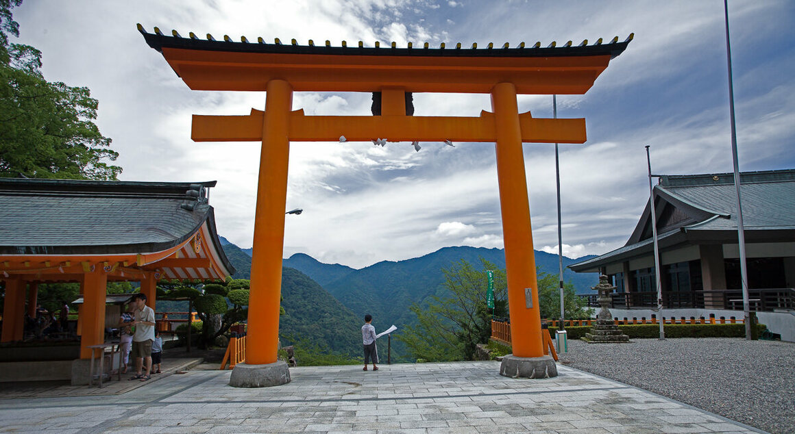 A large torii dwarfs a boy looking out to the valley below at the entrance to the Kumano Nachi Taisha Grand Shrine.