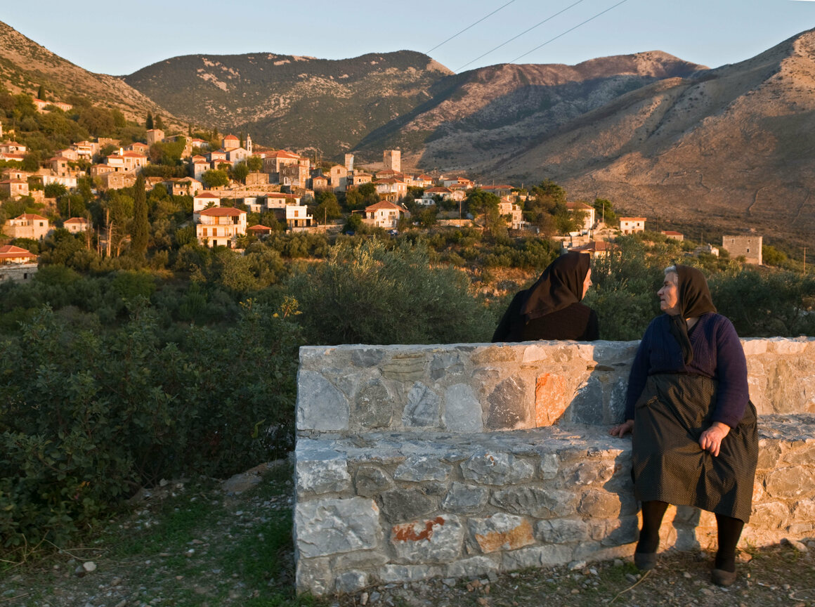 Villagers chatting in the evening light in the Mani village of Langada, Greece.