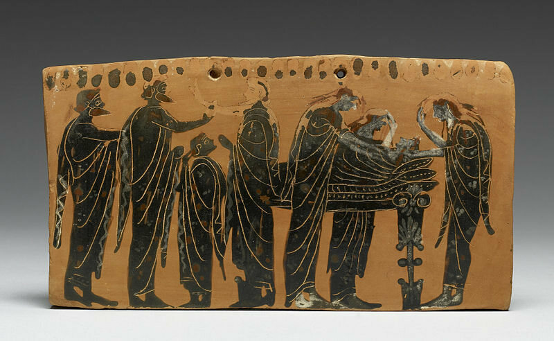 A decorated terracotta plaque, showing the deceased on a bed, surrounded by his family members, some of whom tear their hair in mourning.