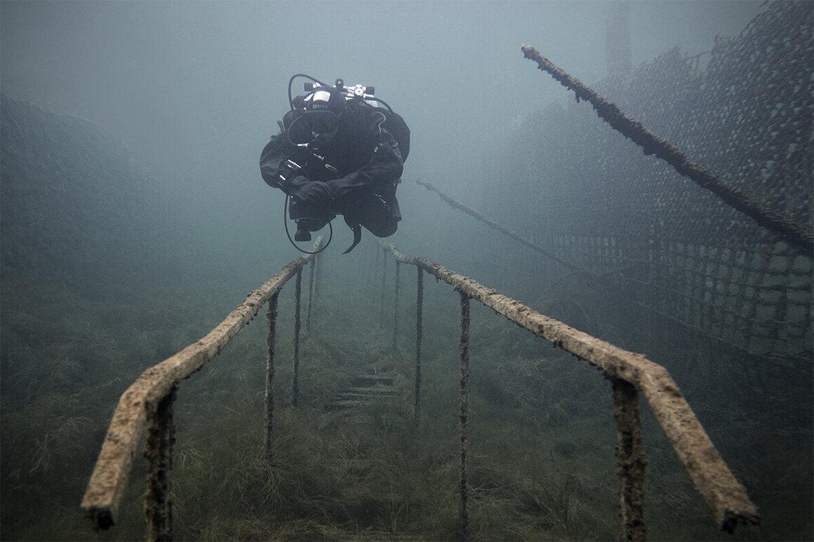 Turun di sepanjang tangga bawah air, di samping pagar penjaga bawah air.