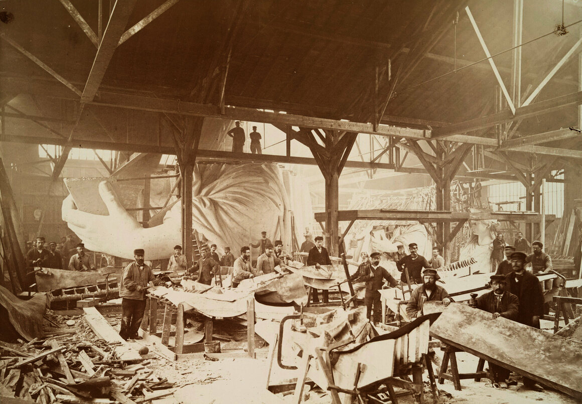 Men in a workshop hammering sheets of copper for the construction of the Statue of Liberty in 1883.
