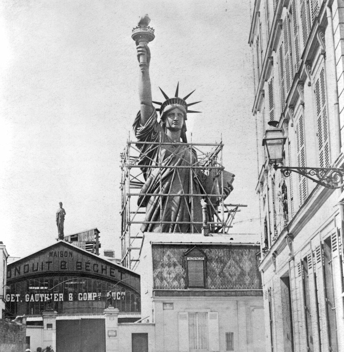 The Statue of Liberty towering over rooftops in Paris.