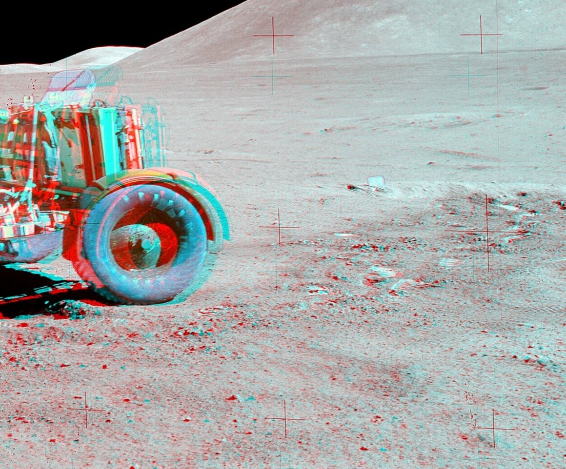 A red-blue anaglyph from an <em>Apollo 15</em> moonwalk. The plaque of <em>Fallen Astronaut</em> can be seen to the right of the rover.
