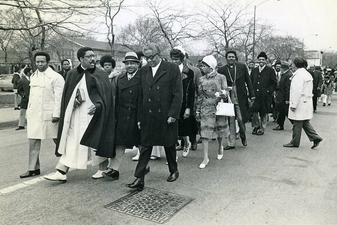 Reverend Clay Evans leads members into the new Fellowship Missionary Baptist Church for opening day celebrations in 1973.