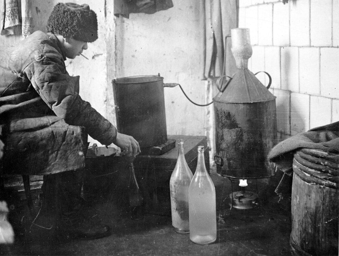 A bootlegger brews the homemade spirit <i>samogon</i>, a precious commodity in post-revolutionary Russia, around 1930.
