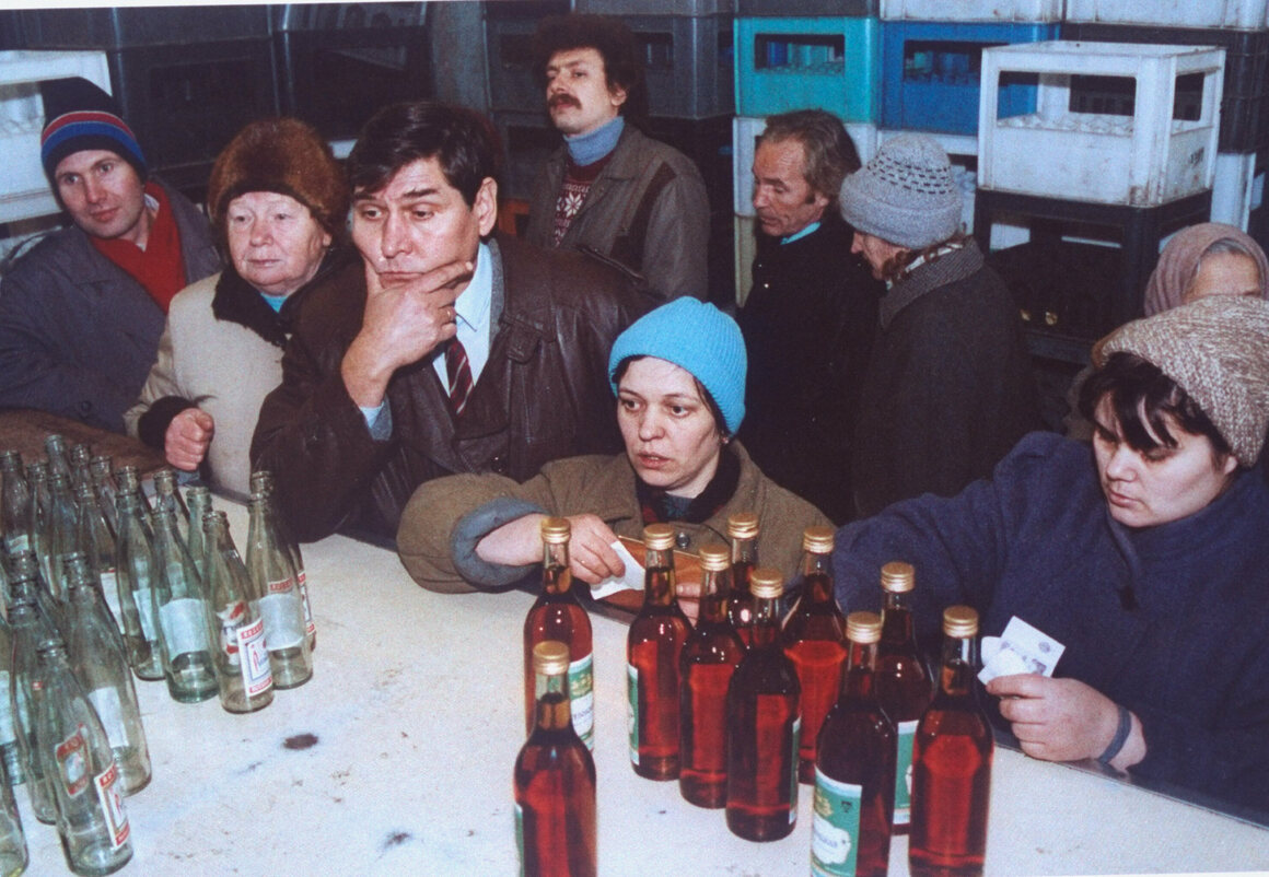 Shoppers on Smolensky Street at a liquor store counter, some with ruble notes in-hand, trying to buy vodka during a shortage.