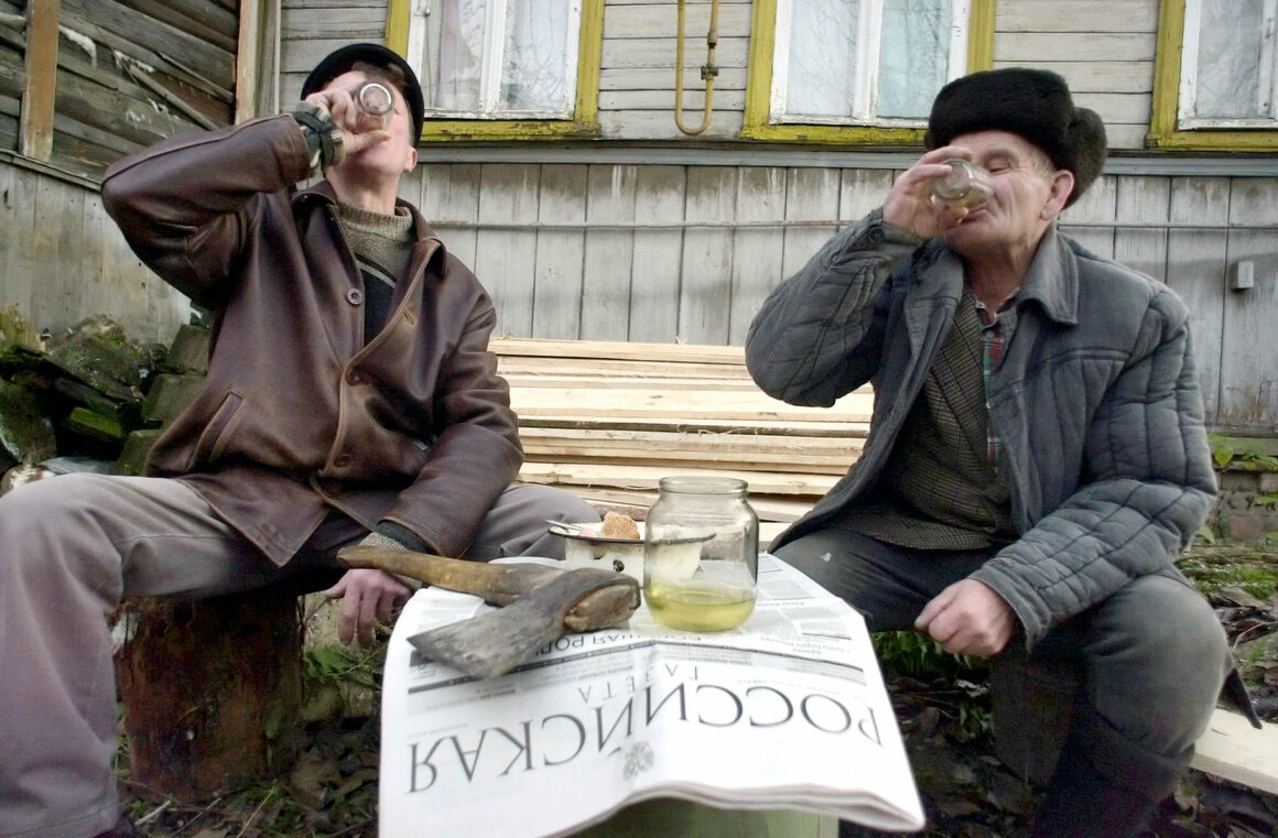 Villagers in the Ivanovo region of Russia drink samogon, a kind of homemade distilled alcohol, in the yard of their house.