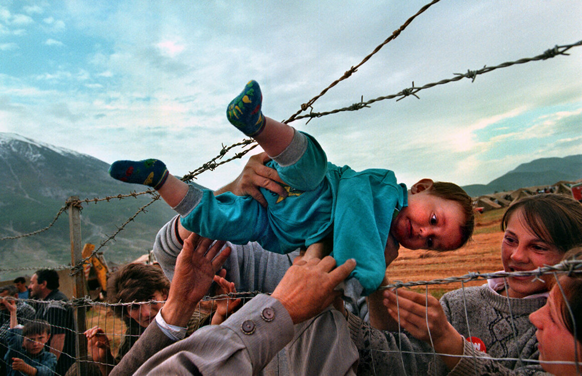 Carol Guzy, <em>Albanian refugee camp</em>, 1999. In 1998, violence against ethnic Albanians in Kosovo led to a wave of refugees. Here, a child is passed to relatives.