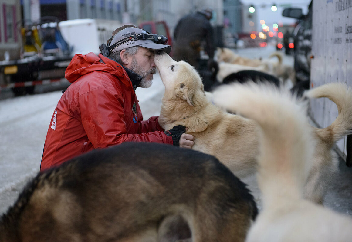 Scott Janssen, also known as The Mushing Mortician, greets each of his dogs before the 2015 ceremonial start.