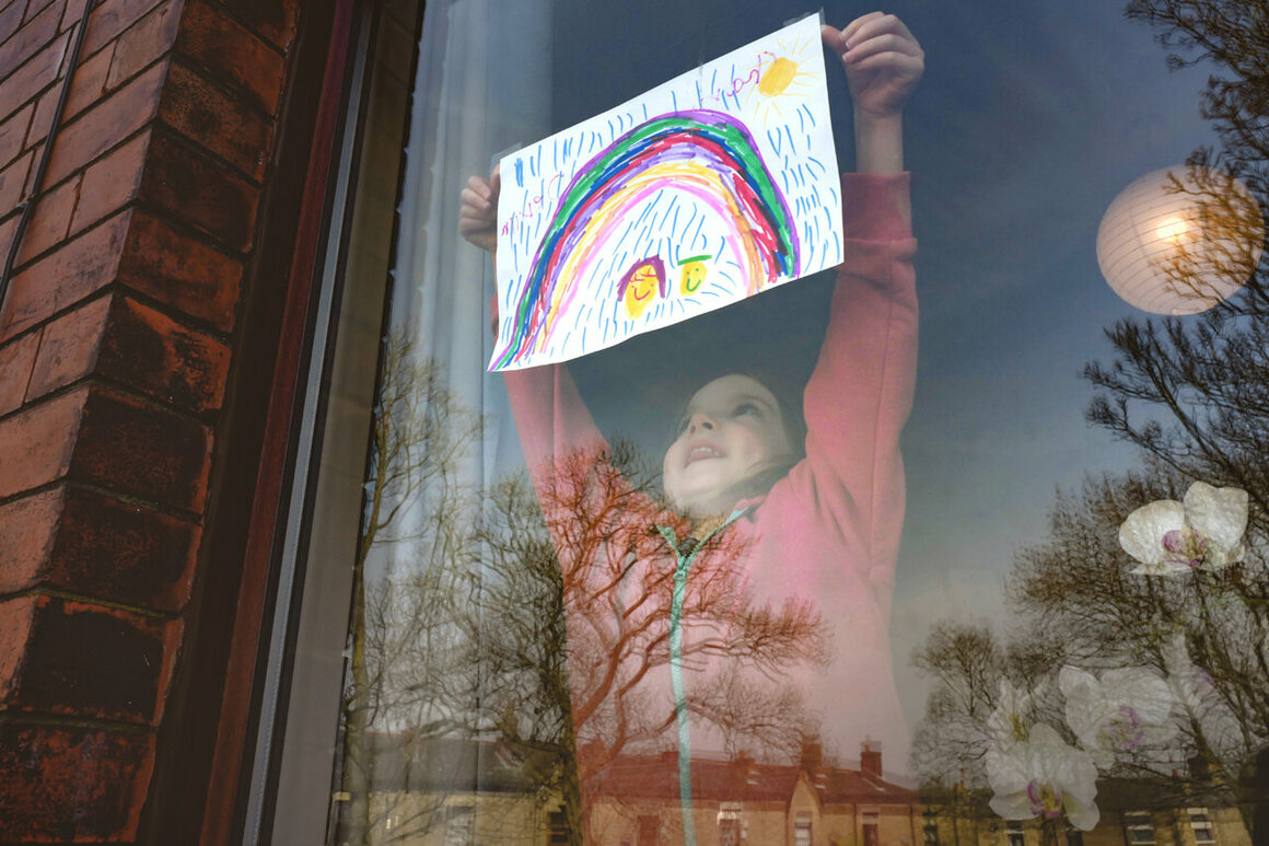 Five-year-old Charlie Rose places a drawing of a rainbow—rainbows in windows are becoming signs of hope and solidarity—in her front window in Manchester, England, on March 24, 2020.