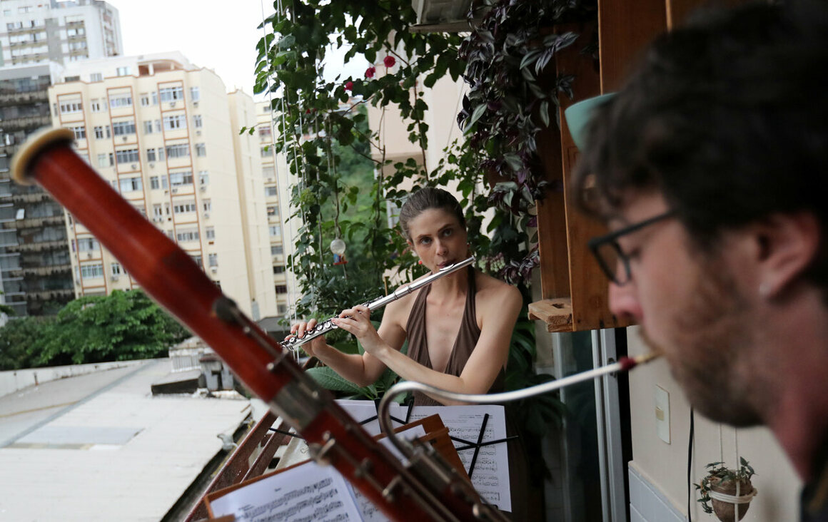 Wife-and-husband classical musicians Sofia Ceccato and Simon Bechemin play on their balcony in Rio de Janeiro, Brazil, on March 21, 2020.