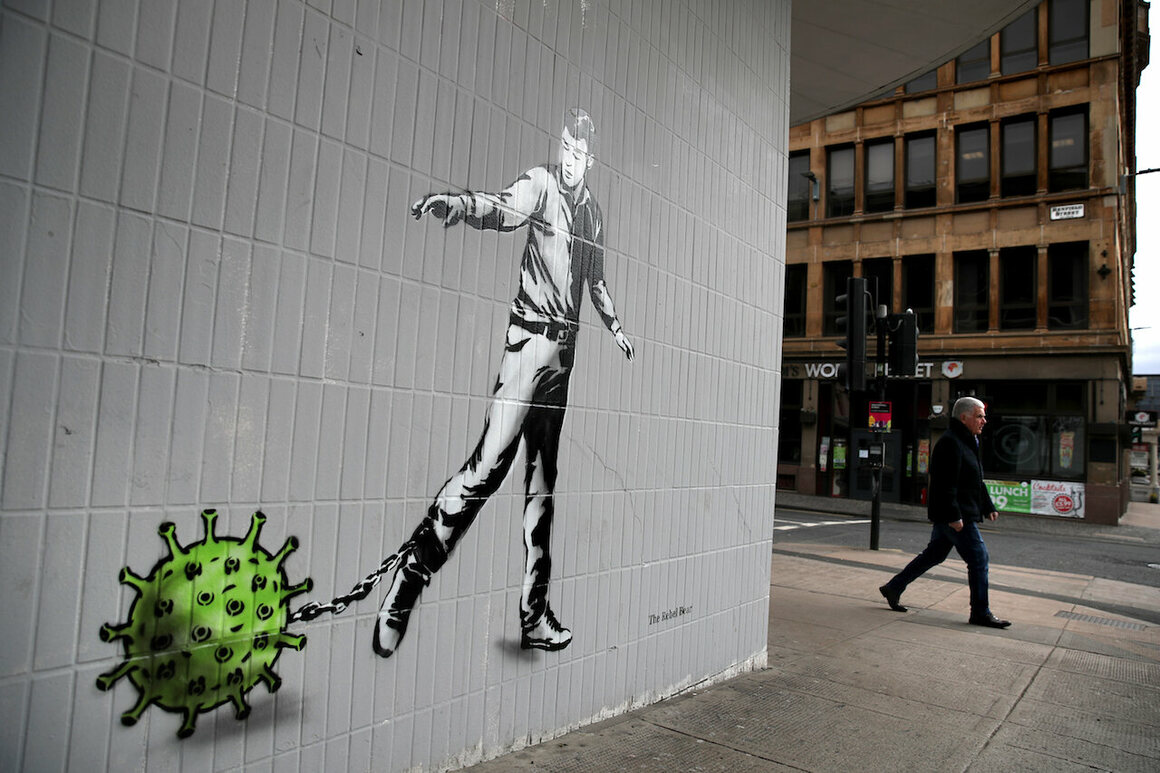 A man walks past art of a person pulling a chain with a germ attached to it, by the artist known as the Rebel Bear, in Glasgow, Scotland, April 3, 2020.