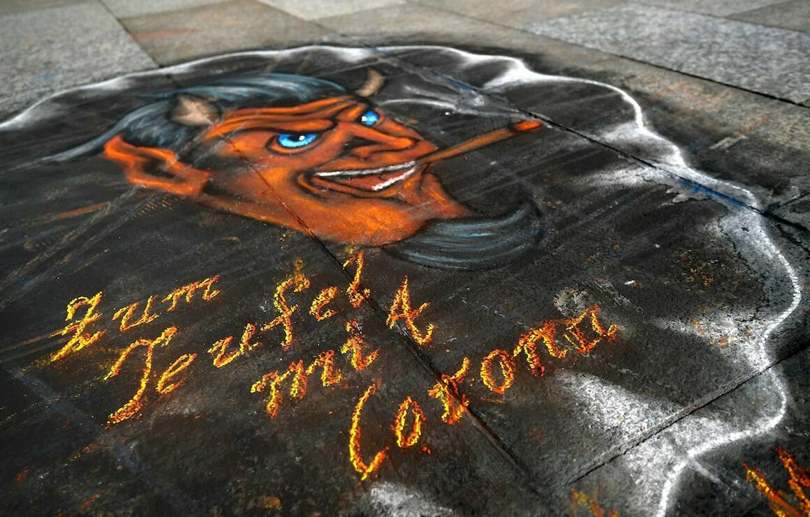 "This graffiti in front of Cologne Cathedral in Germany says ""To hell with Corona,"" March 17, 2020."