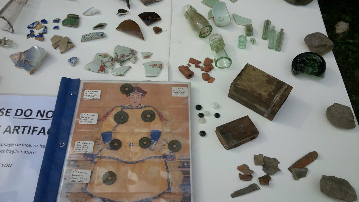 An archaeology display from Barkerville showcases pottery shards, medicine bottles, and Qing Dynasty coins.