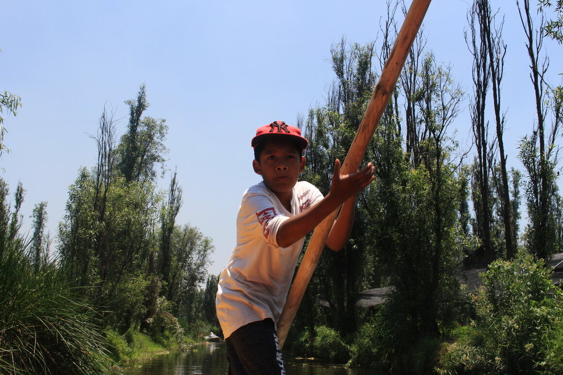 Pedro Capultitla's son, Axel, navigates a trajinera on a canal in Xochimilco. Axel is a 6th-generation chinampero.