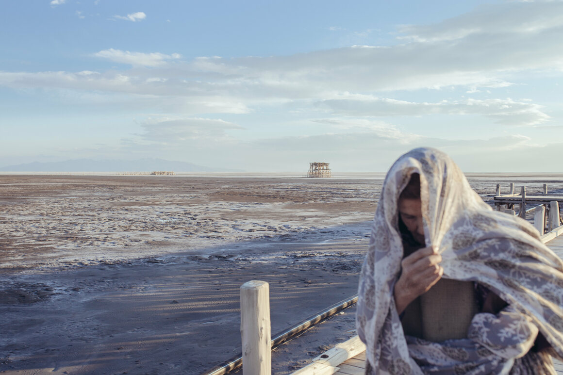 The author's grandmother, Narges, seen here in 2015, walks on a pier on the coast of Sharafkhaneh, where she still lives. Fifteen years ago, before the lake receded too drastically, the whole family met on weekends to eat dinner by the water.