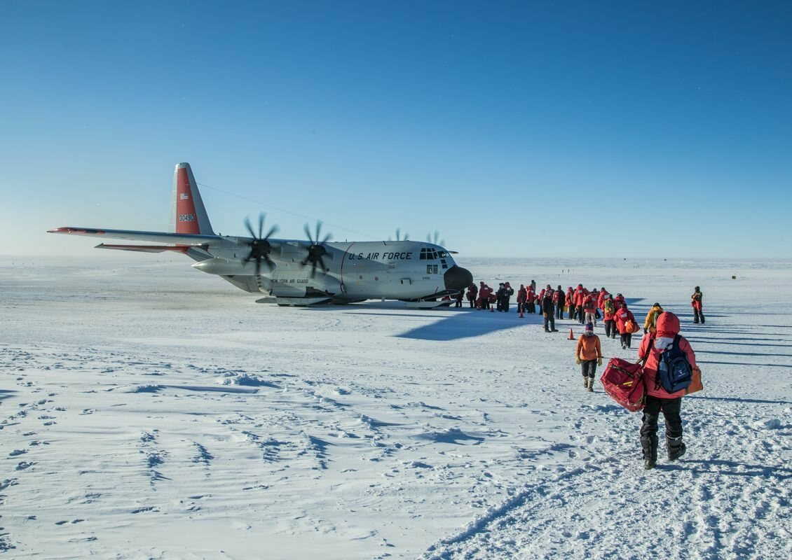 As darkness starts to fall in mid-February each year, a gray C-130 Hercules departs Amundsen-Scott South Pole Station.