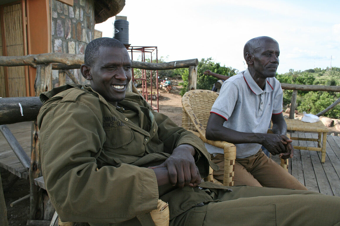 A park guide (left) and Emmanuel Kalisa (right), a local herder.