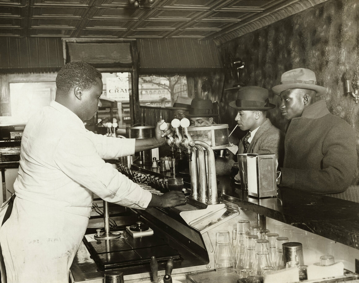 An undated photograph showing African-American men at a soda fountain.
