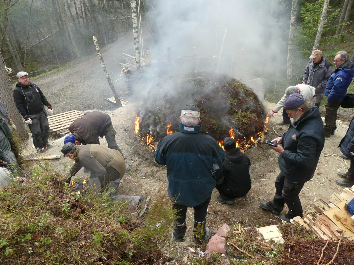 Trehylsen er dekket med lag med hakket kull.  Brannen, som kan brenne i opptil tre dager, frigjør tjære samlet inn nedenfor.