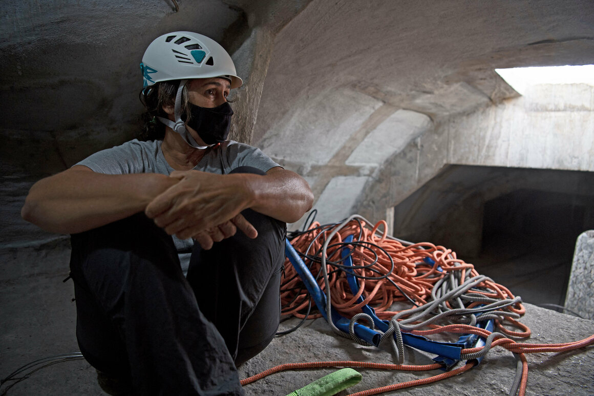 Architect Cristina Ventura sits inside a crawlspace in the statue, which provides access to its upper reaches.