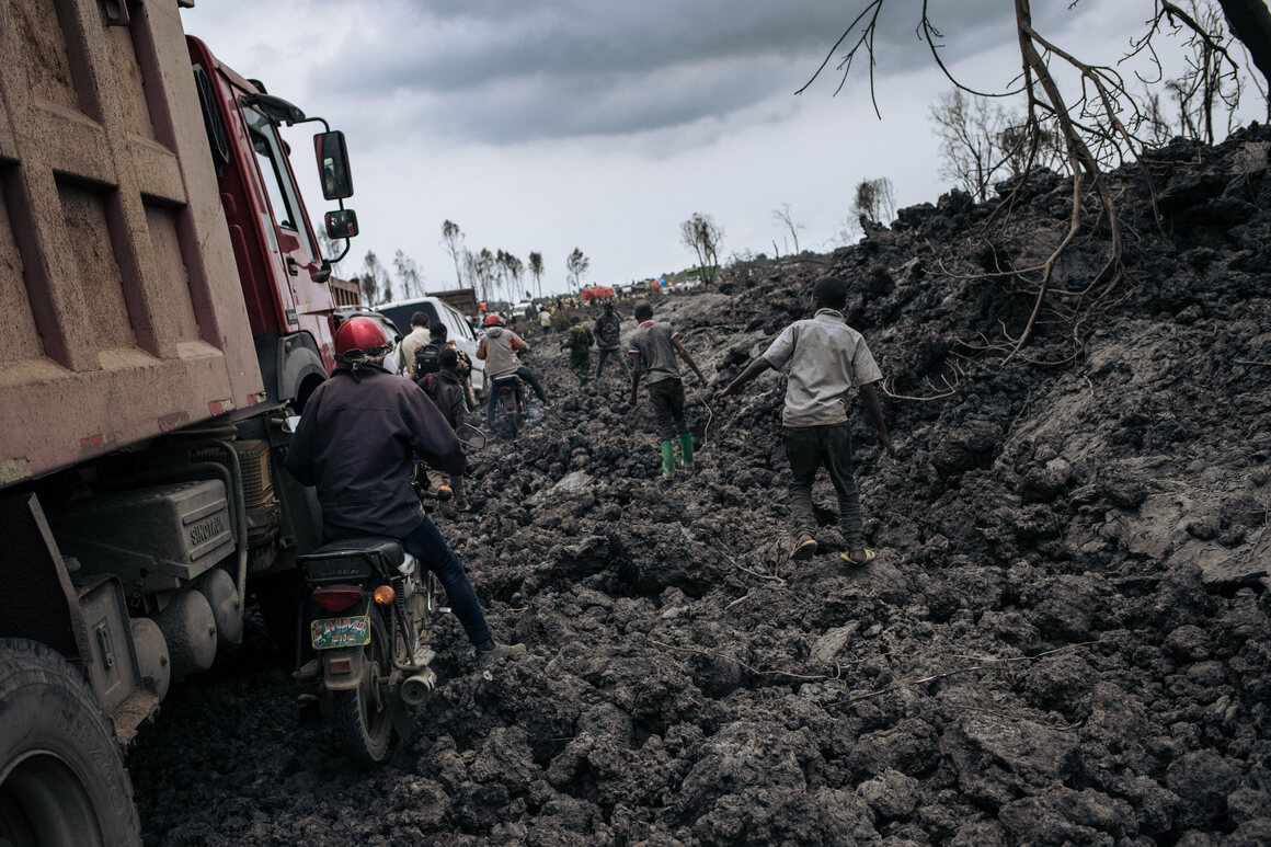 Motorbikes and trucks make their way through the solidified lava flow in the northern neighborhoods of Goma.