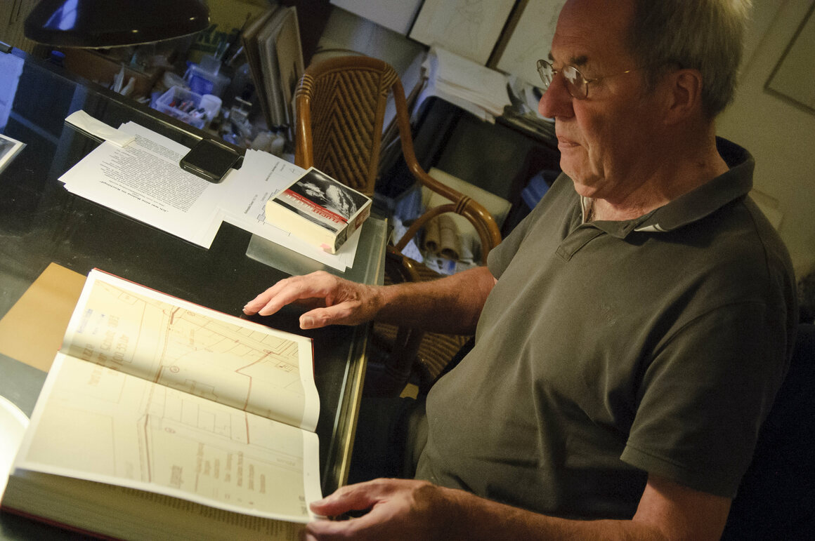Andreas Springer looks at a book with a map of Tunnel 57.