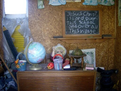The interior of one of the houses, made up to look like an old-fashioned schoolhouse, complete with teacher and students.