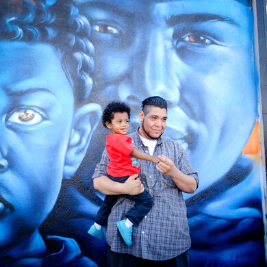 Adam Ayala (Smile South Central founder) in front of a mural by Artist Zina @illuzina