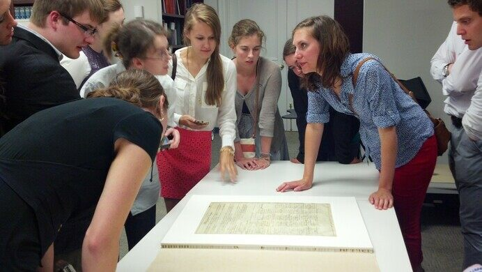 Curators discuss documents with a group.