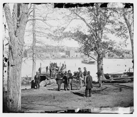 Guards at ferry landing on Mason's Island examining a pass