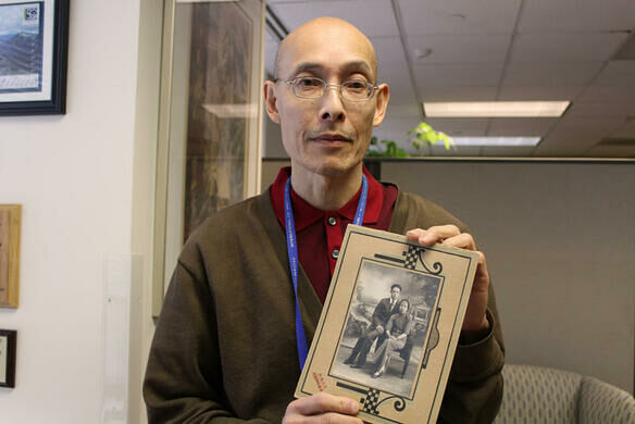 Ron Chew holding a portrait of his immigrant parents
