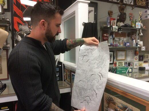 Tattoo artist Bryan Kachel holds a sketch for a sleeve design