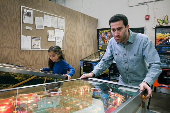 Adam and his daughter Maya playing pinball.