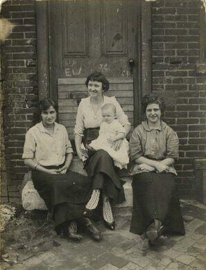 Three women and infant sitting on doorstep, Philadelphia.