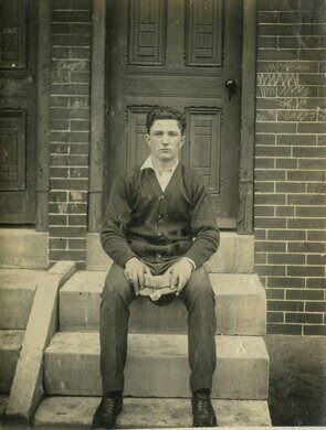 Young man in cardigan sweater sitting on marble steps, Philadelphia.